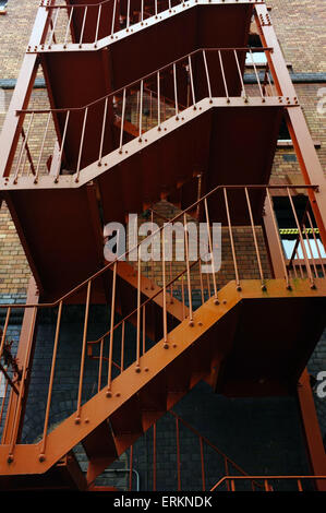 An external metal fire escape running up the side of a building in Bristol - Stock Photo