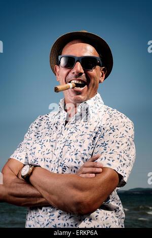 Man with cigar on the beach - Stock Photo