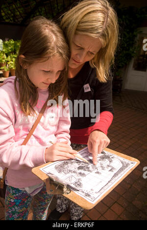 Mother and 9 year old daughter perusing map prior to embarking on an African trail in search of the extinct Quagga - Stock Photo