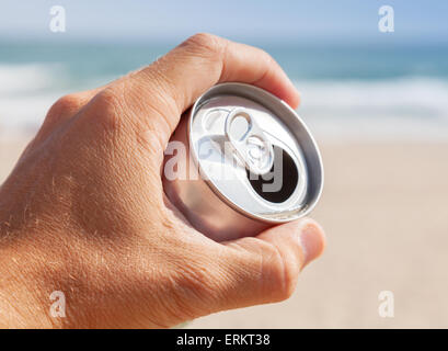 Aluminum can of beer in male hand with blurred beach and sea on a background - Stock Photo
