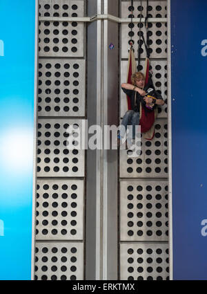 Munich, Germany. 04th June, 2015. A demonstrator climbs up the front of the main train station to hang a banner - Stock Photo