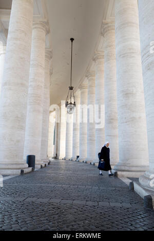 The colonnades and nun in St. Peter's Square (Piazza San Pietro), Vatican City, Rome, Lazio, Italy, Europe - Stock Photo