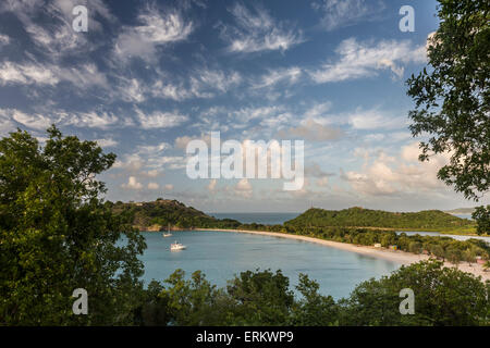 The clouds are illuminated by the setting sun on Deep Bay a stretch of sand hidden by lush vegetation, Antigua, - Stock Photo