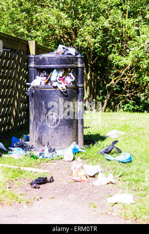 overflowing waste bin garbage trash on floor council cutback cutbacks UK England mess messy dog poo bags strewn - Stock Photo