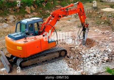 Large hydraulic Jackhammer Smashing Rocks - Stock Photo