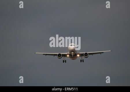 Commercial airliner on final approach - head-on view. - Stock Photo