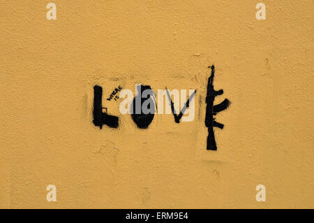 Guns and knives form the word love. Abstract stencil graffiti urban art on textured wall. - Stock Photo