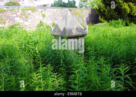The top of a tombstone in an overgrown graveyard in Bristol. - Stock Photo