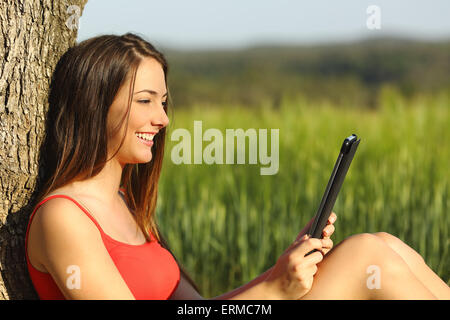 Girl reading an ebook or tablet sitting in a green field leaning in a tree - Stock Photo