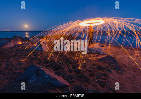 Silhouette of man spinning illuminated wire wool at night, Hayling Island, Blue Flag Beach, Hampshire, England, - Stock Photo