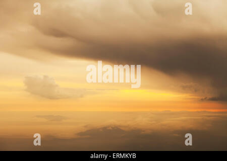 Dramatic clouds over mountains as seen from the air at sunset. - Stock Photo