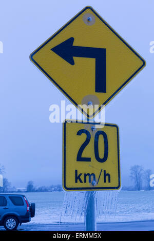 Road sign indicating speed at left turn with icicles hanging from it; British Columbia, Canada - Stock Photo