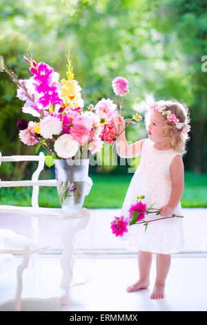 Little girl arranging flowers at home in a vase. Child playing indoors. Kids birthday party. Children giving flower - Stock Photo