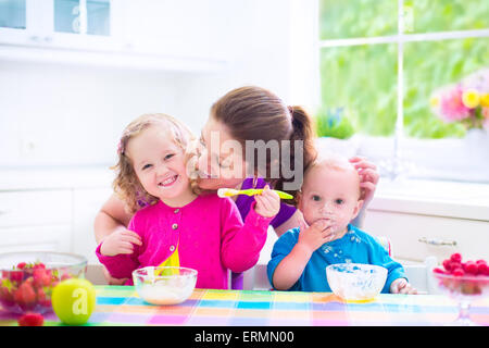 Happy family, mother with two children, toddler girl and funny messy baby boy having healthy breakfast eating fruit - Stock Photo
