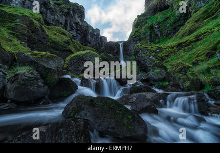 An unnamed stream flows over a cliff face creating a beautiful waterfall after a period of heavy rains; Iceland - Stock Photo