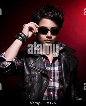 Portrait of handsome teen boy wearing stylish sunglasses and leather jacket over dark red background, teenage fashion - Stock Photo