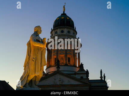 Schiller sculpture on Gendarmenmarkt square in front of the dome of the French Cathedral in the evening, Berlin, - Stock Photo