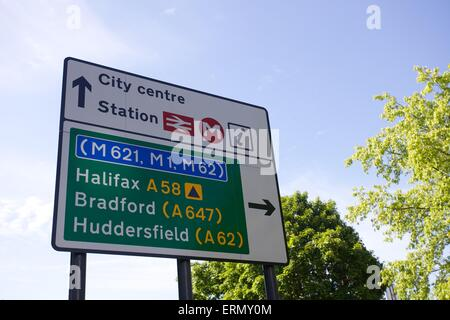 Road sign in leeds city centre marking directions for Halifax A58 Bradford A647 and Huddersfield A62 - Stock Photo