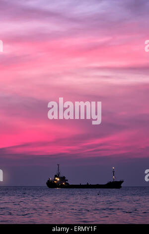 Cargo ship in South China Sea at dusk, Vietnam - Stock Photo
