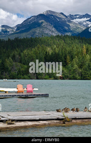Beautiful Green Lake in Whistler in the summer.  Forest and mountains.  Colourful chairs on a dock, and mallard - Stock Photo