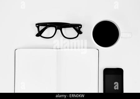 high-angle shot of a blank notebook, a pair of black plastic-rimmed eyeglasses, a cup of coffee and a smartphone - Stock Photo
