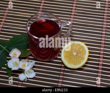 glass of red tea with a lemon on a rug - Stock Photo