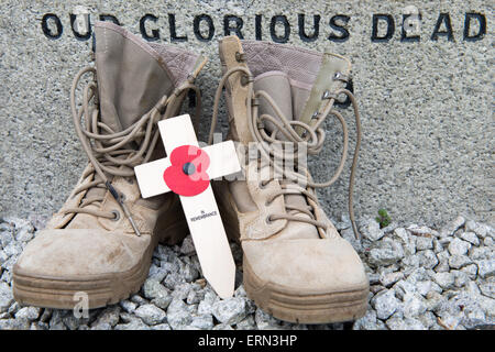 Lest We Forget....a pair of modern British desert combat boots on a World War 1 memorial with a cross and poppy. - Stock Photo