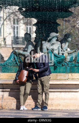 Young couple at Fountain.looking at pictures on tablet.  Rosio square. Lisbon Portugal. - Stock Photo