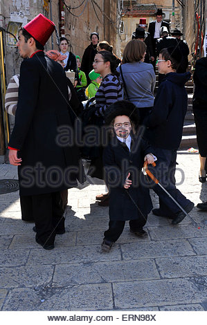 Ultra-Orthodox Jews in the street of Jerusalem's Mea Shearim neighborhood. Purim is a celebration of the Jews' salvation - Stock Photo