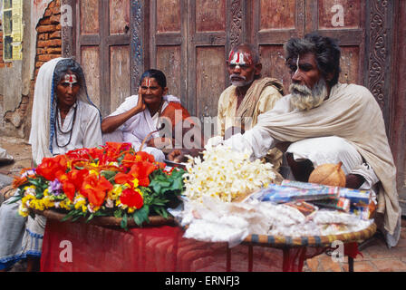 Four 'sadhu' and 'sadhvi' are seated in the street. They are staying behind flowers on sale ( Nepal) - Stock Photo