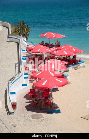 The beach in the Algarve town of Armacao de Pera southern Portugal Bar with red umbrellas on the seafront - Stock Photo