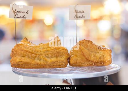 Fresh baked spinach and potato burekas on display stand - Stock Photo