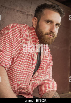 Portrait of bearded young man with gauged ears and stylish hair - Stock Photo