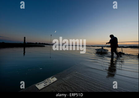A man pulls his rowing boat onto a quay in Bosham West Sussex - Stock Photo