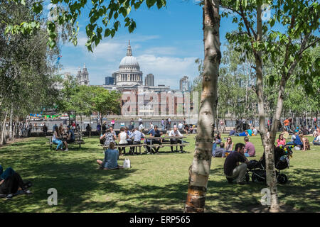 People relaxing in Tate Modern gardens, with St Pauls Cathedral in background, Southbank, London UK - Stock Photo