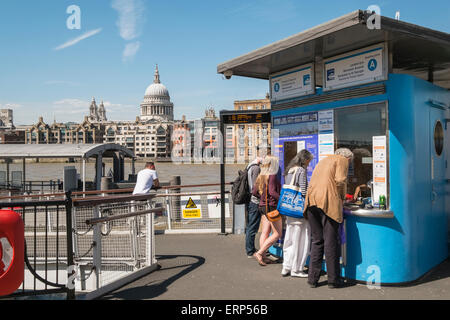 People buying tickets at Bankside Pier for boat journey on River Thames, London UK - Stock Photo