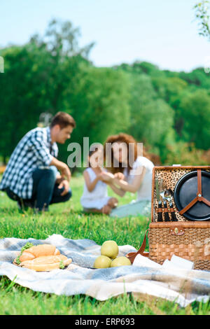 Happy family on a lunch in the park - Stock Photo