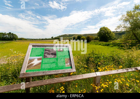 Interpretative sign about Westbury White Horse chalk figure, which is seen in the background. - Stock Photo
