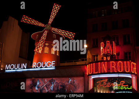 Red mill of famous Moulin Rouge cabaret & night club in Paris by night, France - Stock Photo