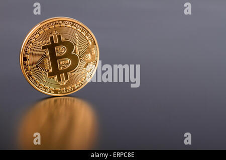 Studio shot of golden Bitcoin virtual currency on gray. Close-up of front side. - Stock Photo