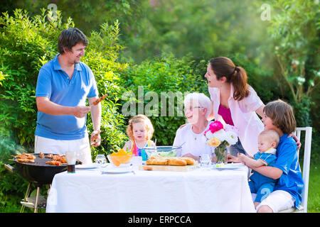 Grill barbecue backyard party. Happy big family enjoying BBQ lunch with grandmother eating meat in the garden with - Stock Photo