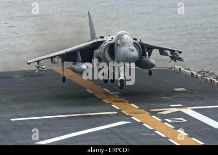 A U.S. Marine Corps AV-8B Harrier II fighter aircraft lands on the flight deck of the amphibious assault ship USS - Stock Photo