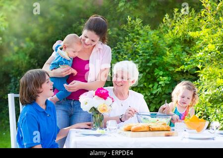 Happy grandmother having lunch with her family - young woman and three children, eating grilled meat, salad, bread - Stock Photo
