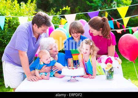 Big family with three kids and grandmother enjoying birthday party with cake blowing candles in garden decorated - Stock Photo