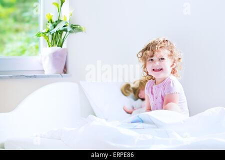 Funny curly toddler girl waking up on a early sunny morning in a white bedroom with window playing with her toys - Stock Photo