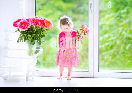 Cute happy toddler girl with curly hair wearing a pink dress playing with a bunch of beautiful big peony flowers - Stock Photo