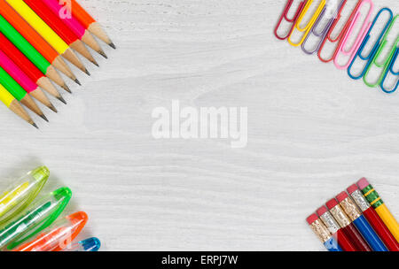 Bright colorful pencils, pens and paper clips on all white wooden desktop corners. High angled view in horizontal - Stock Photo