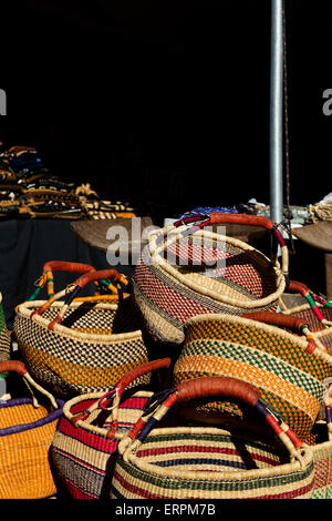 Colorful, woven baskets piled high at African Art Village of popular Tucson Gem and MIneral Show in Tucson, Arizona. - Stock Photo