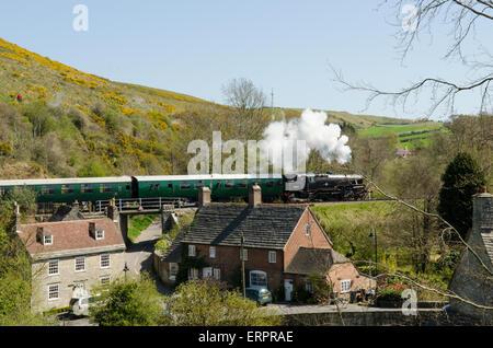 Steam train crossing railway bridge in Corfe, Dorset, April, pulling carriages. - Stock Photo