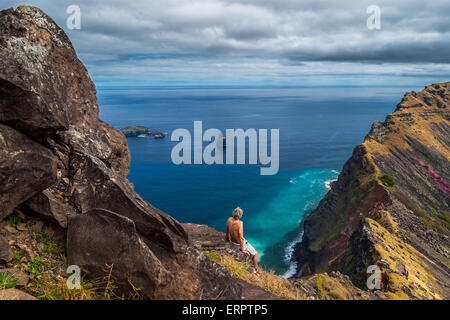 Back of a man sitting on a cliff looking out over the sea at the rim of the crater of Rano Kao, Easter Island, Chile - Stock Photo